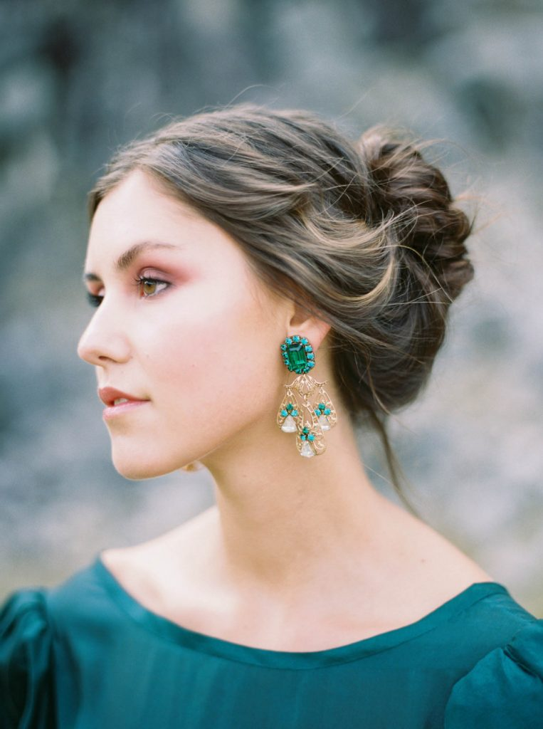woman with Jane Austen-inspired hairstyle, emerald green dress and earrings