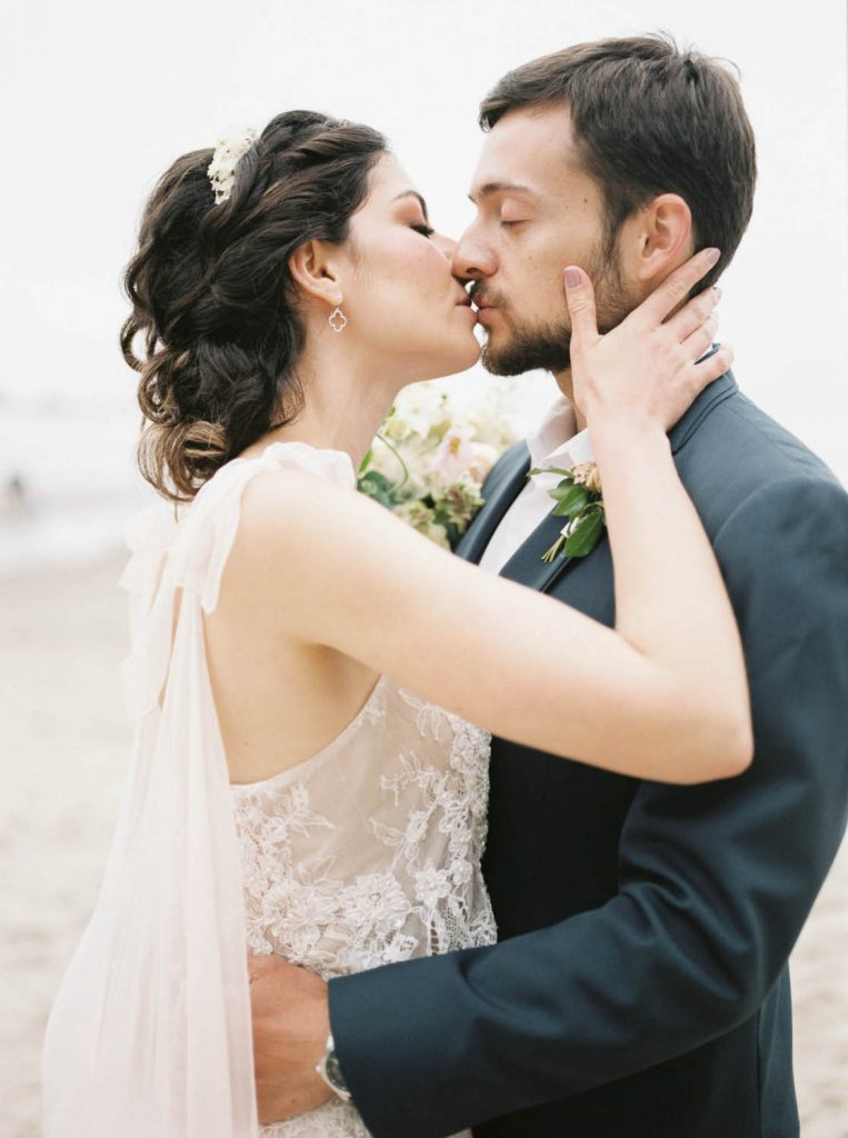 bride and groom embrace in kiss with eyes closed by Amanda K photo