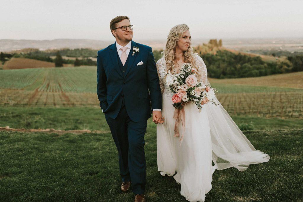 bride and groom pose after wedding overlooking Black Walnut Inn vineyard