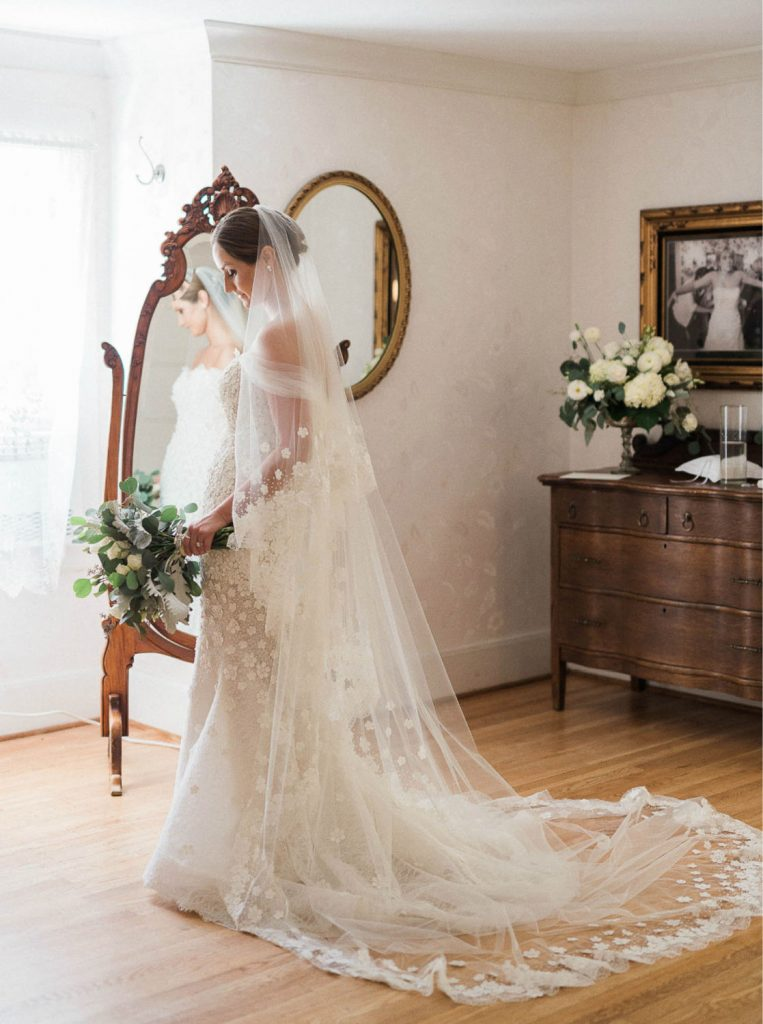 bride wearing couture dress and veil looks in full length mirror