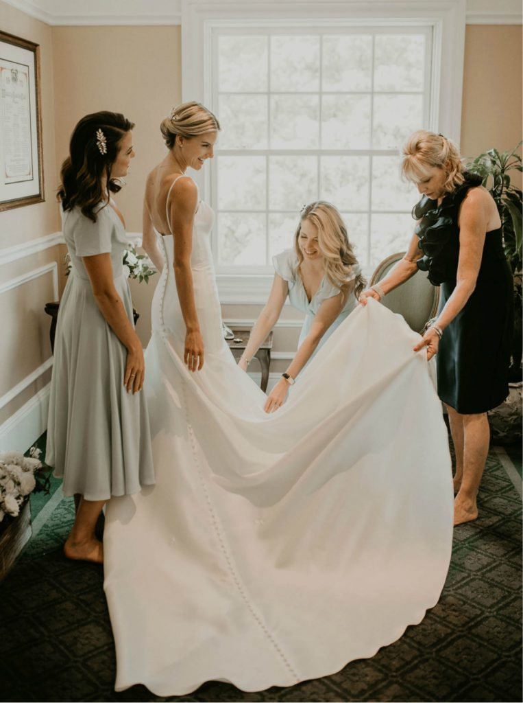 bride surrounded by mom and sisters getting dressed