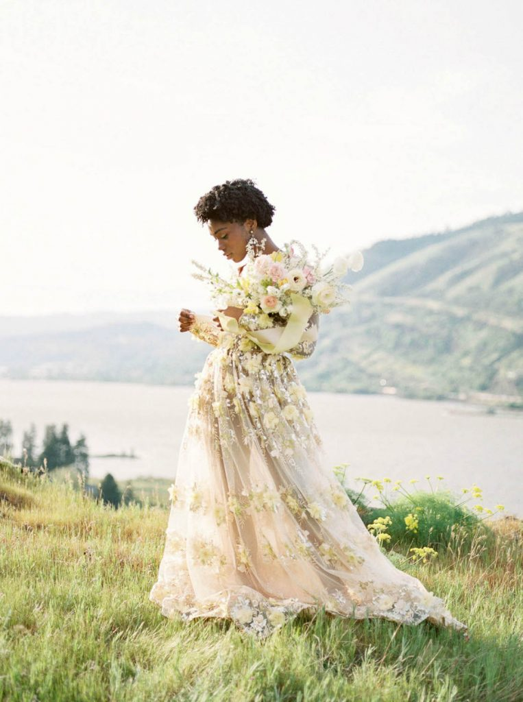 woman wearing one of a kind sheer wedding dress by Emily Riggs holding bouquet by Selva Floral