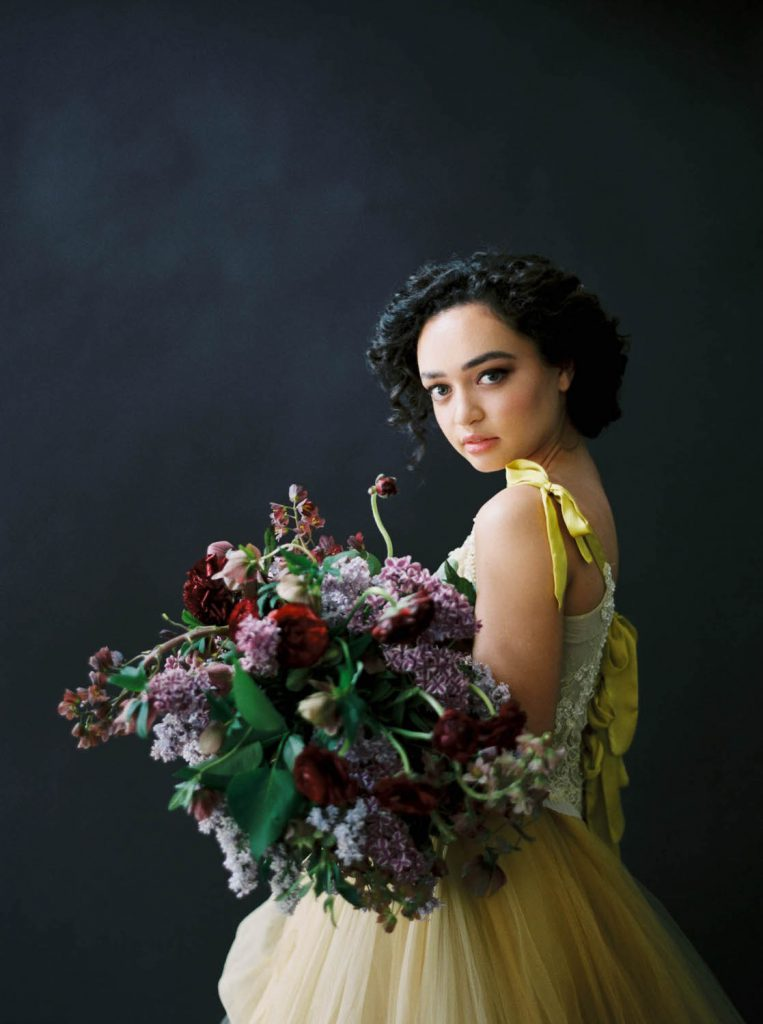bride wearing bright yellow wedding dress from Claire La Faye with armful of flowers against a dark background