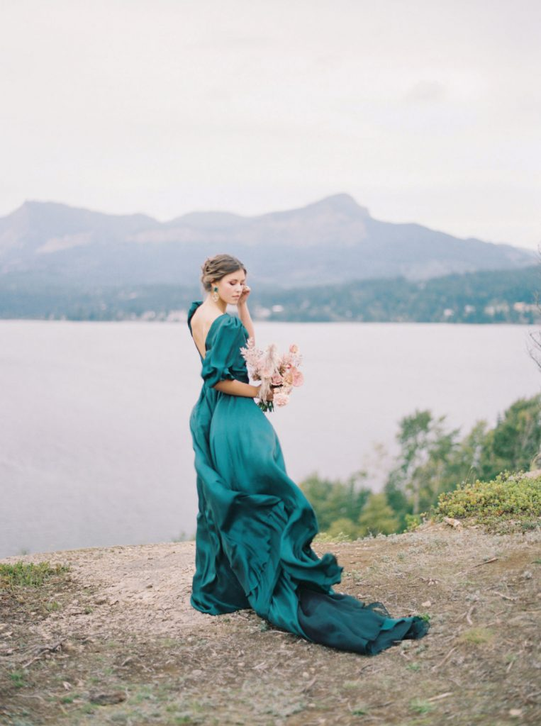 pure silk emerald green dress with puffed sleeves floating in the wind