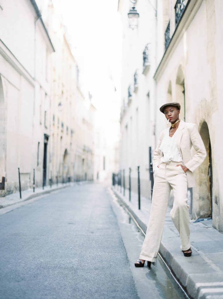 androgynous Parisian woman wearing linen suit and hat smoking in the streets of Le Marais