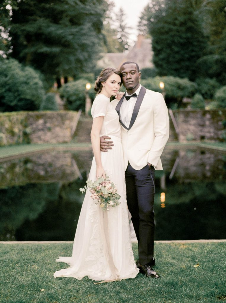 smoldering embrace of bride in Alexandra Grecco and groom in white tuxedo jacket in front of reflecting pond at Lewis and Clark College