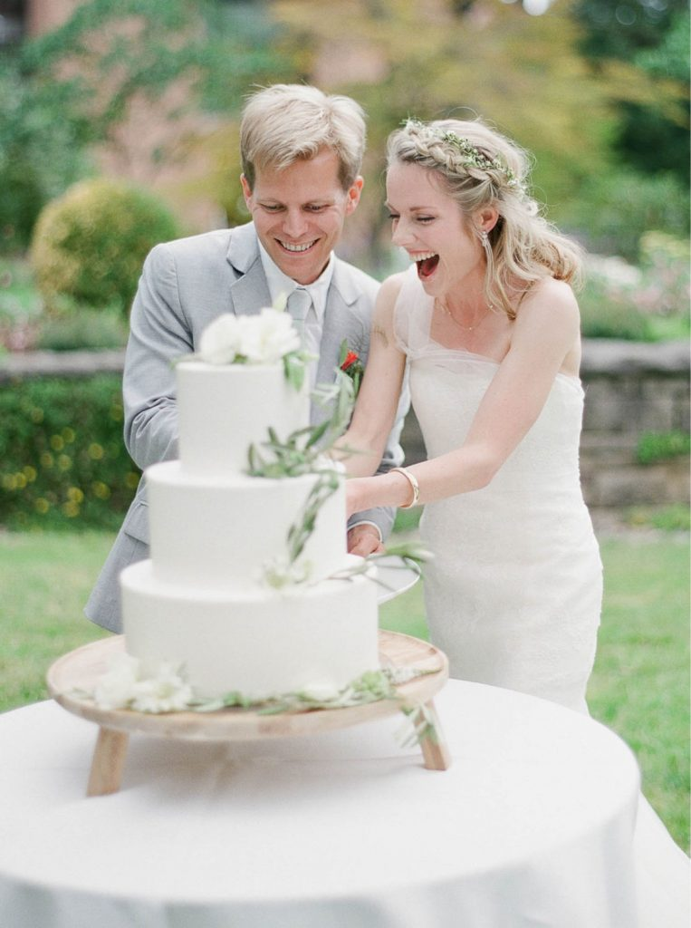 bride and groom smiling and cutting wedding cake at Lewis and Clark College