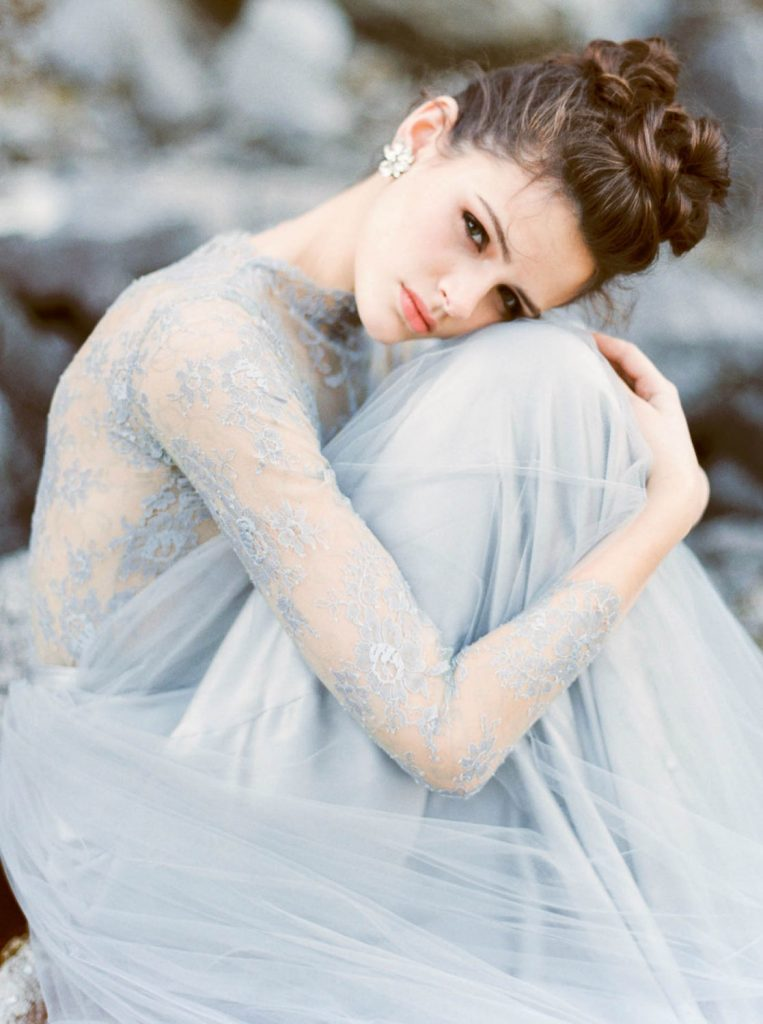 bride hugging her knees wearing pale blue lace and silk tulle dress by Emily Riggs and shot by Maria Lamb
