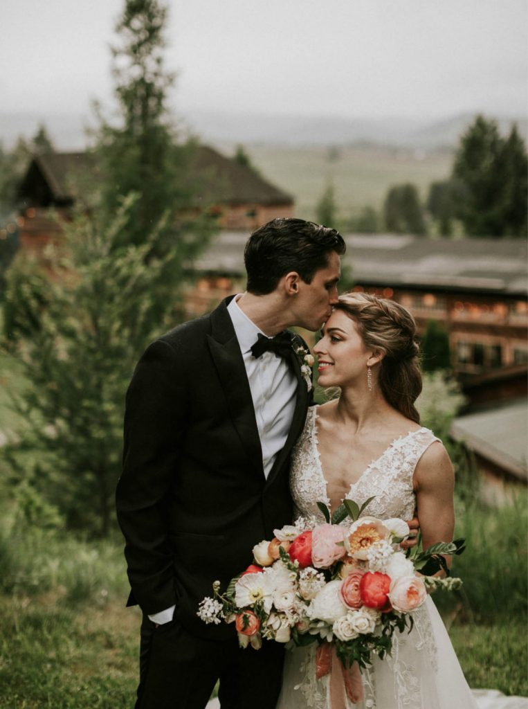 groom kissing bride's forehead with Mt. Hood Organic Farms in background