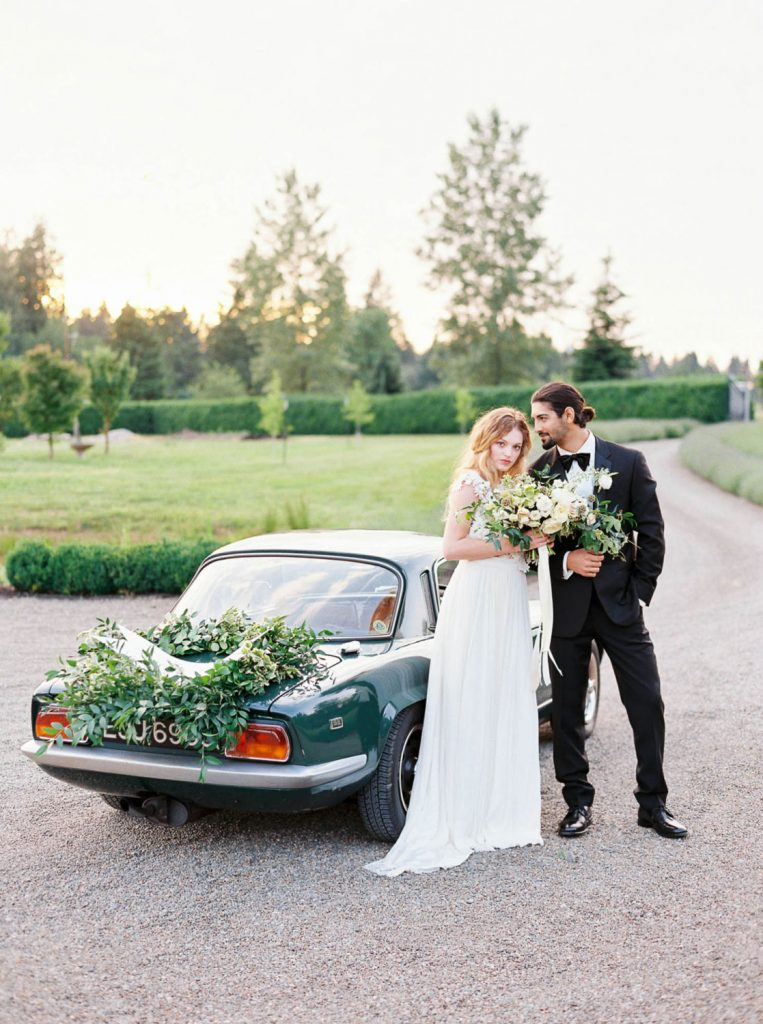 bride and groom pose next to decorated elopement getaway car