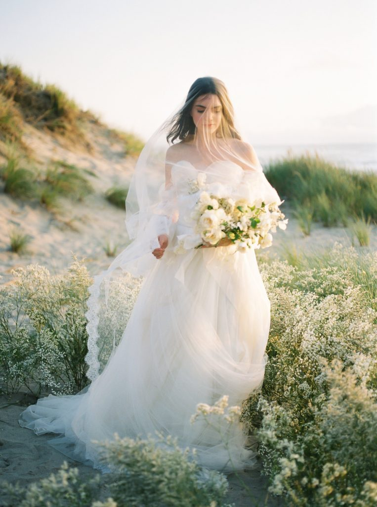 bride standing in golden light on sand dune covered with veil holding flowers