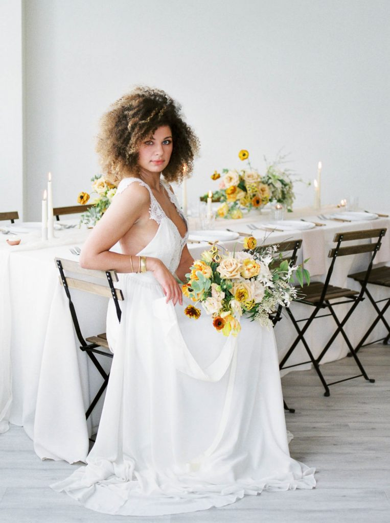 bride with natural kinky curly hair holding neutral colored bouquet by Swoon Floral Design