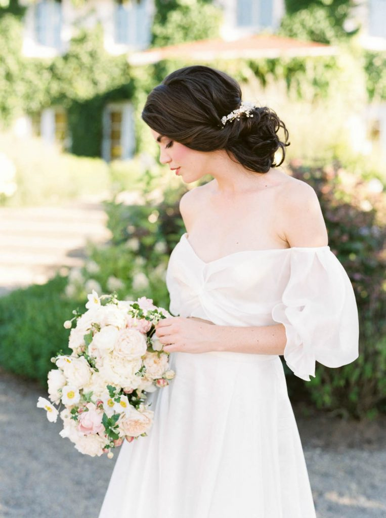 bride standing at Monet Vineyards wearing two piece puffed sleeves dress by Flora Bridal from The Dress Theory Seattle