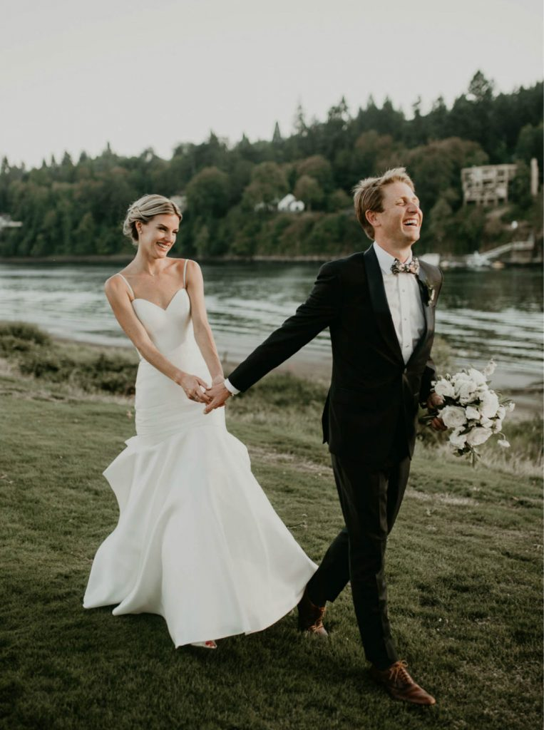 groom laughing holding bouquet while leading bride