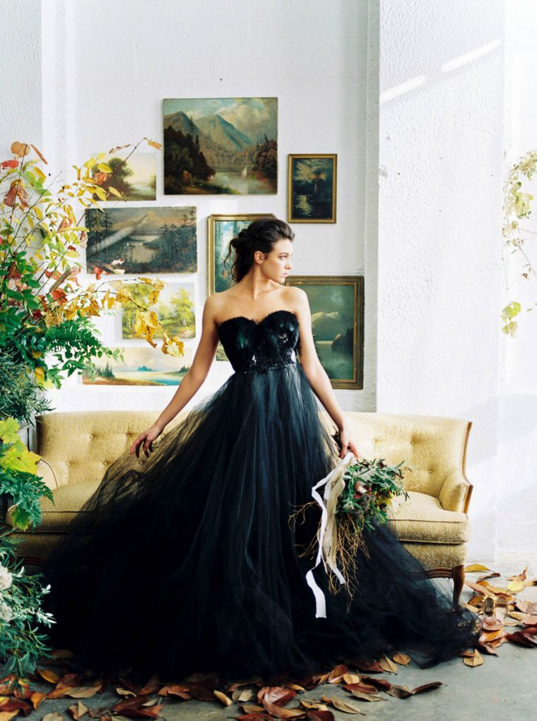 bride in black wedding dress surrounded by fall leaves and vintage paintings