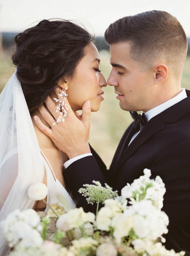 groom holding bride's face and leaning in to kiss her