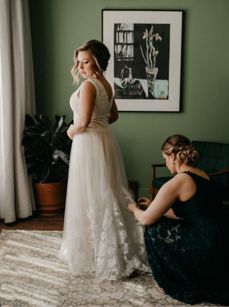 bride looks out window while bridesmaid tends to the bustle