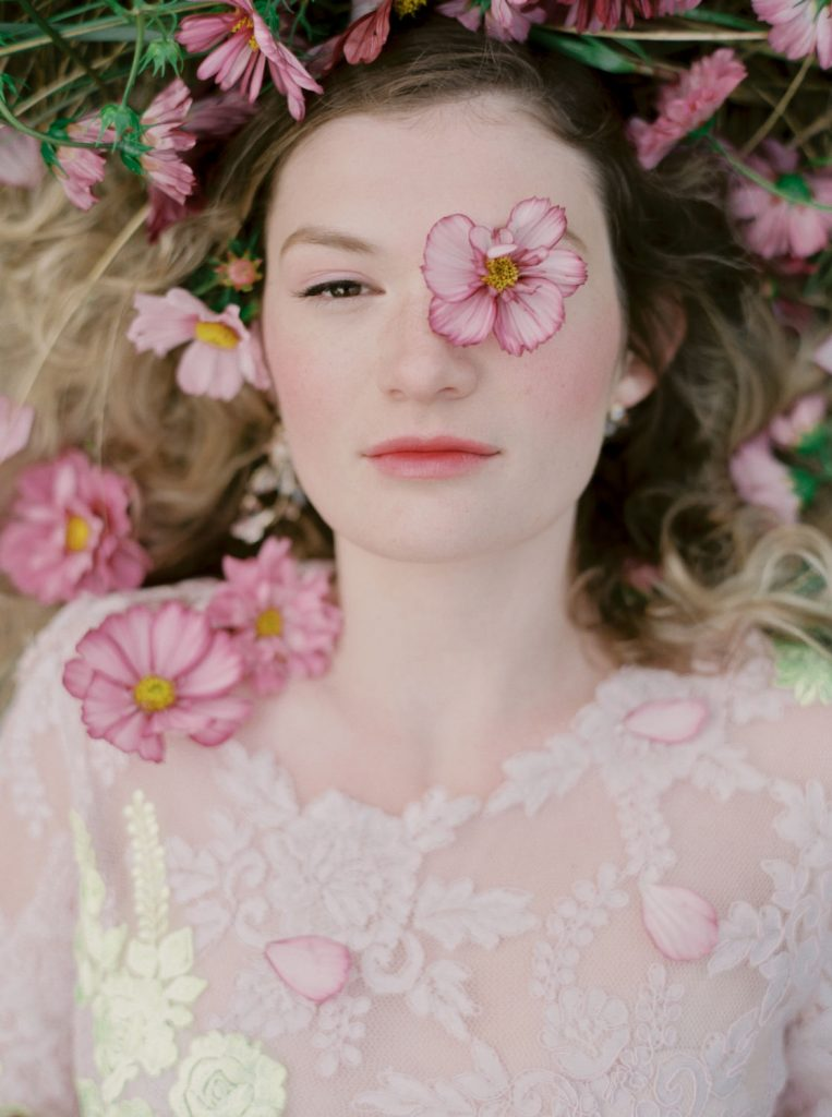 girl wearing pale violet lace dress lying in pink flowers with pink cheeks and lips