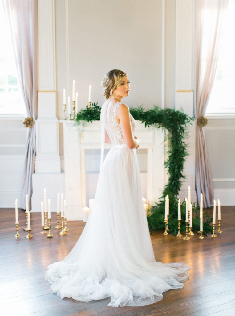 bride standing by luxurious fireplace surrounded by greenery and candles