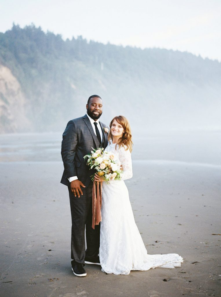 couple poses on beach after eloping in Oregon