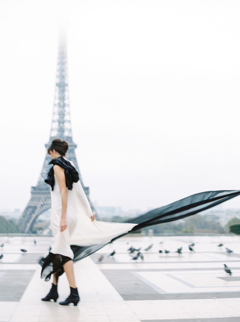 rear view of woman in black and white dress and french twist hairstyle in front of Eiffel tower