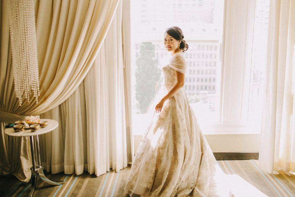 bride wearing golden Oleg Cassini gown standing in glowing window light