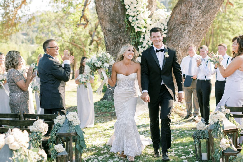 just married couple walks down the aisle by flower adorned tree at home