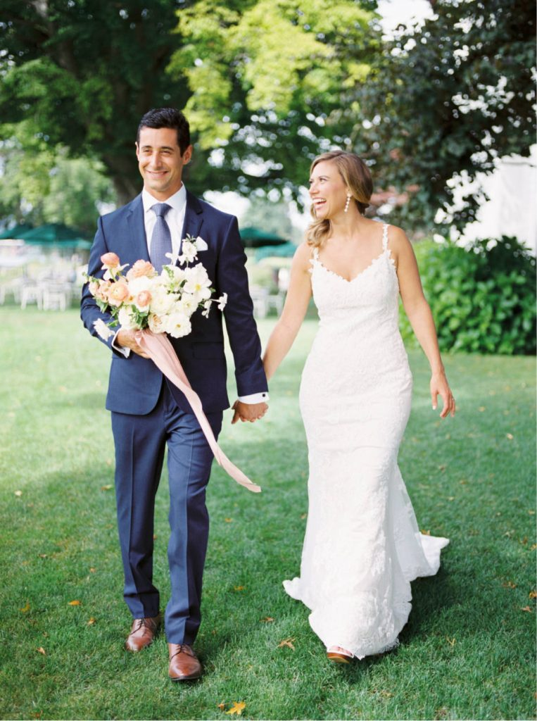 groom smiling and holding hands with bride who wears light natural makeup