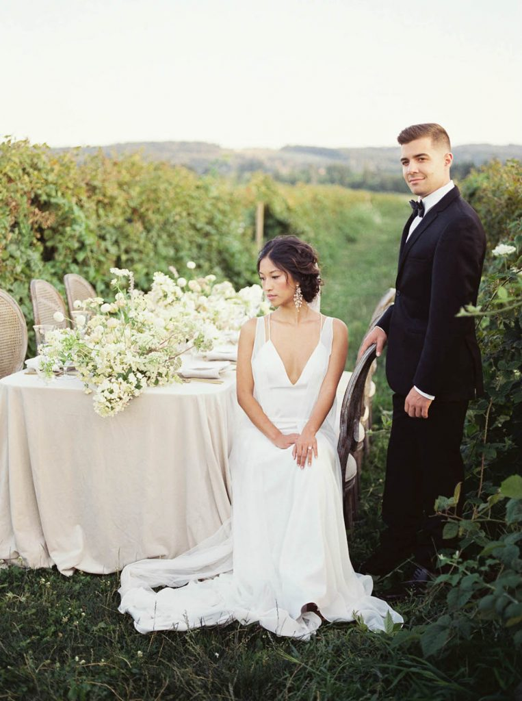 bride and groom looking at their intimate dinner table in raspberry field