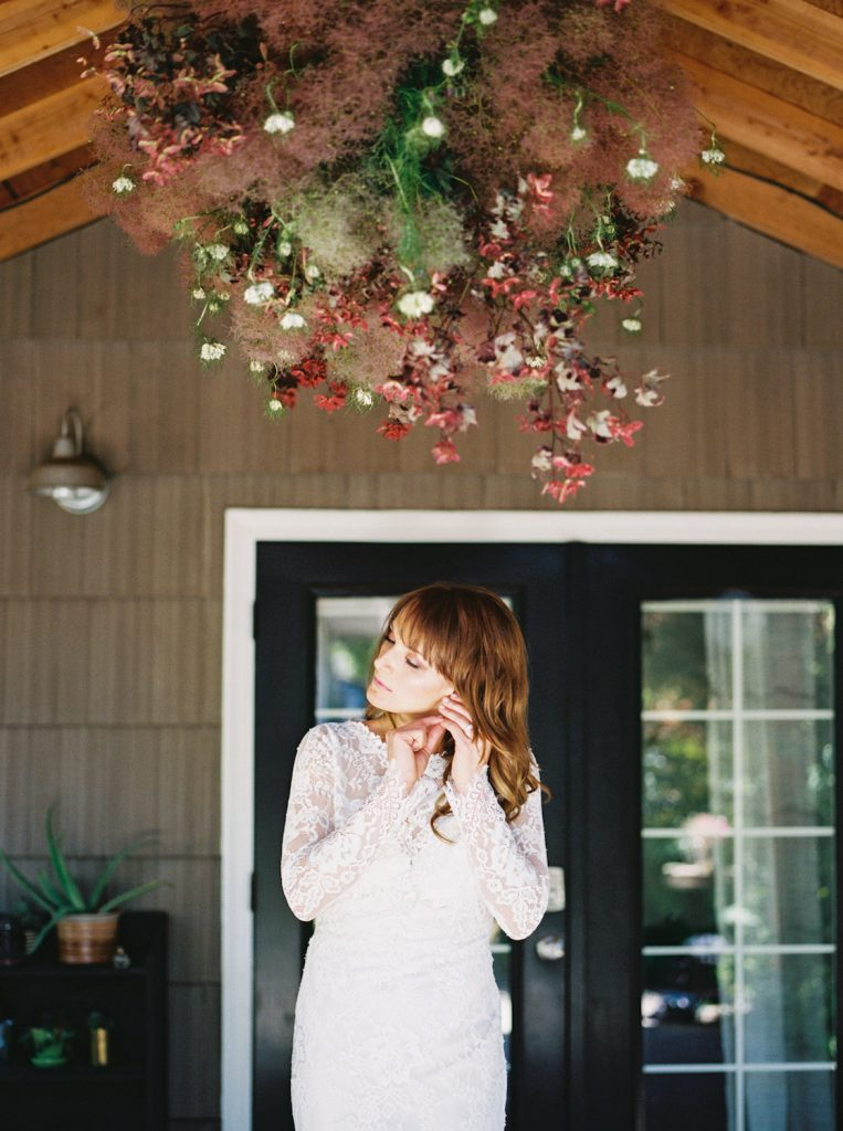 bride standing under floral installation by Sea of Roses shot by Justin Douglas Photography