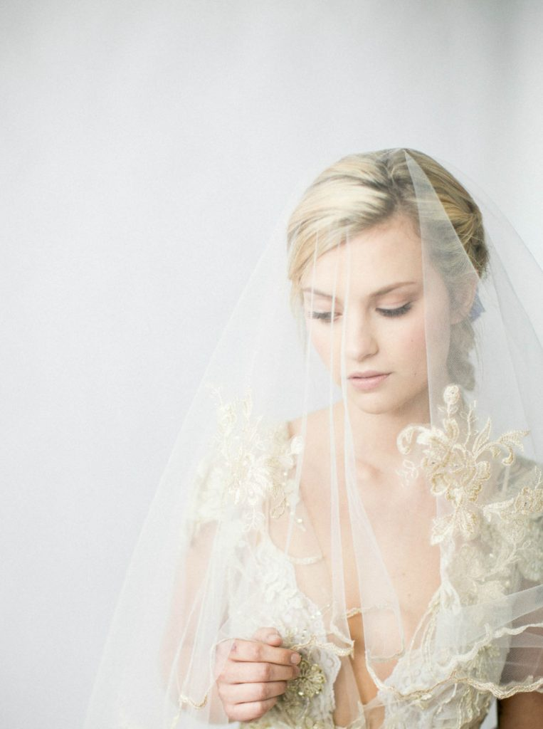 portrait of bride wearing gold wedding dress and gold veil