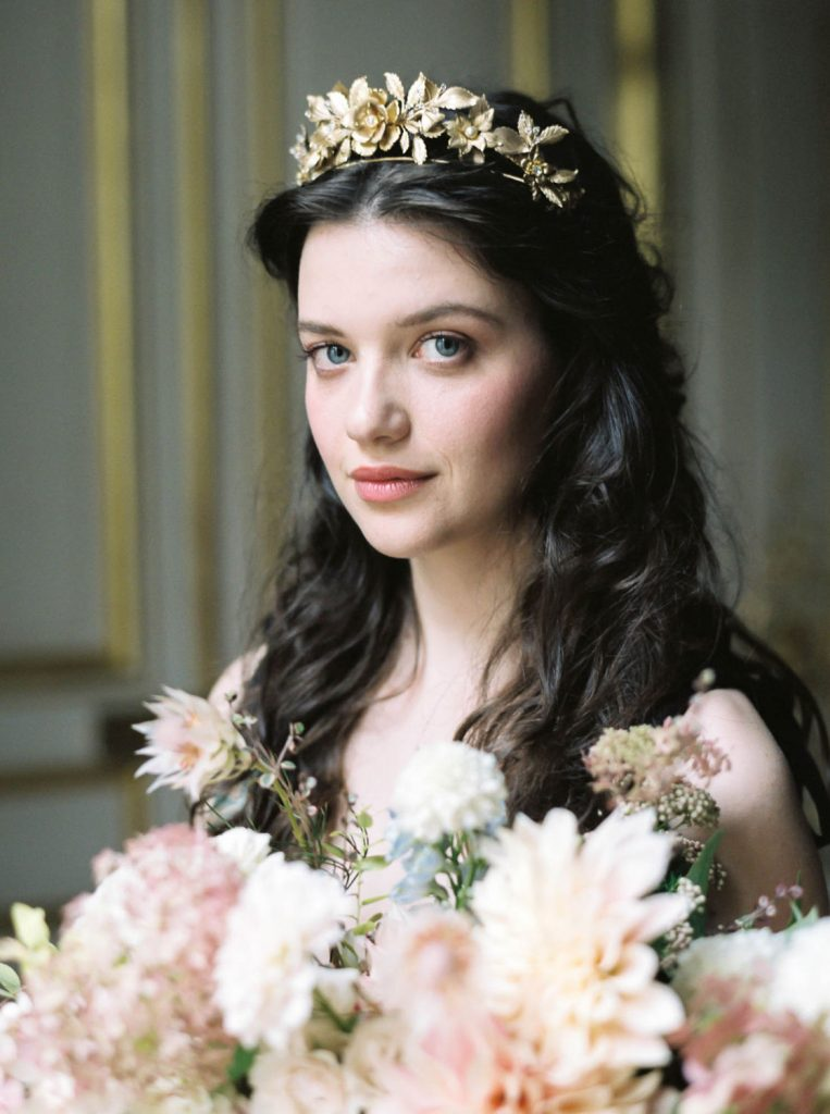 brunette woman with pretty, natural makeup and half up waves wearing gold floral crown and holding armful of blush dahlias