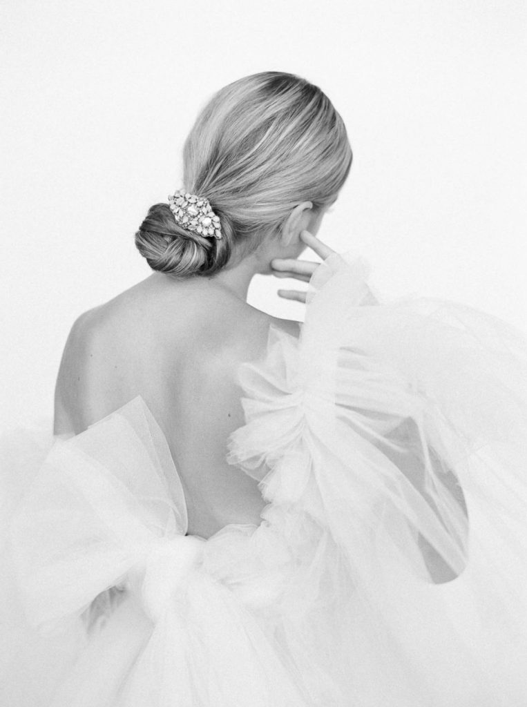 black and white film image of bride with smooth chignon and tulle wedding dress ready for The Ritz Portland
