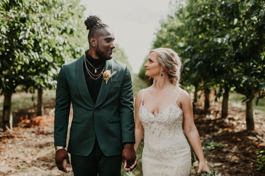 groom wears hunter green suit and bride wears green earrings