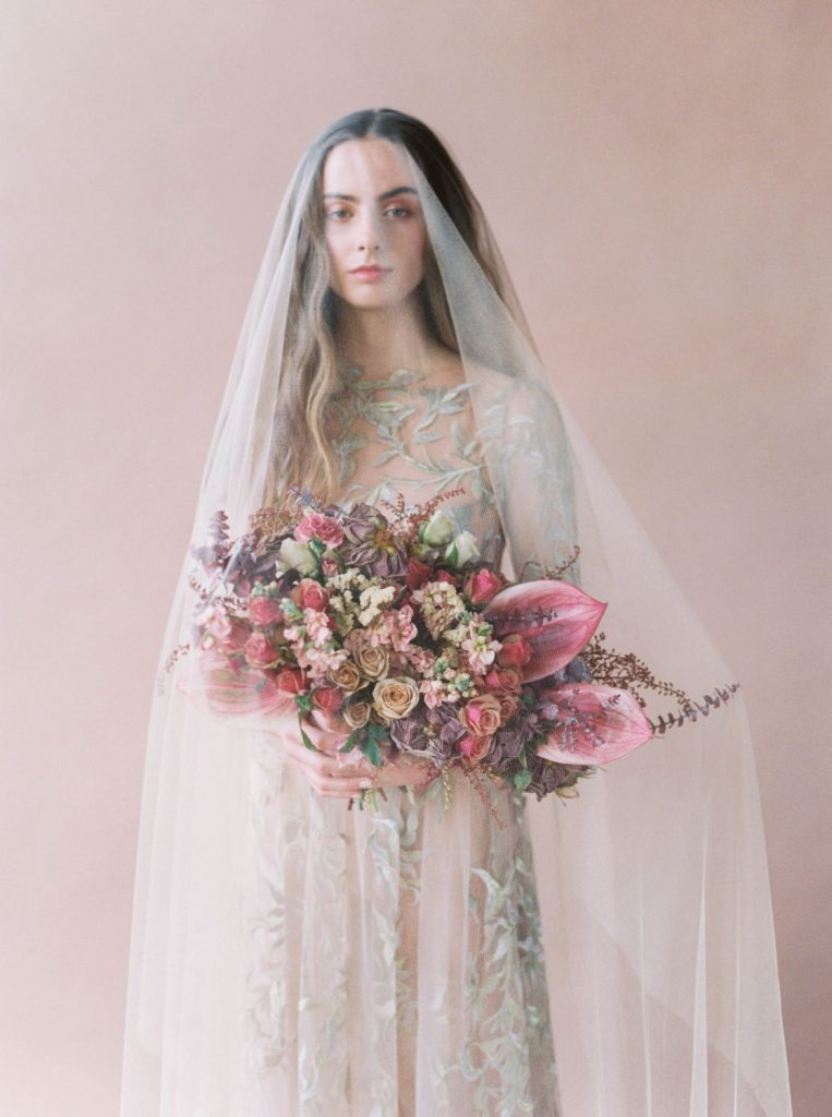 sheer veil covering long-haired bride holding bright pink bouquet by Ponderosa and Thyme
