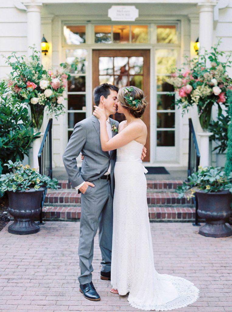 bride and groom kiss in front of venue doorway