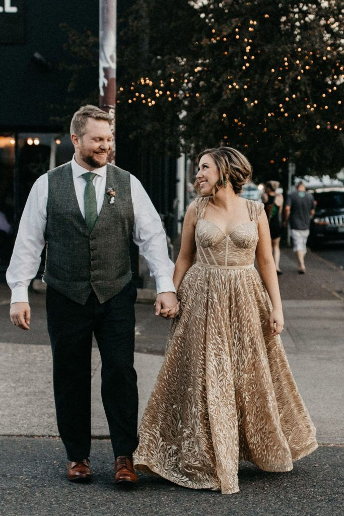 bride and groom strolling outside of Coopers Hall during their wedding reception
