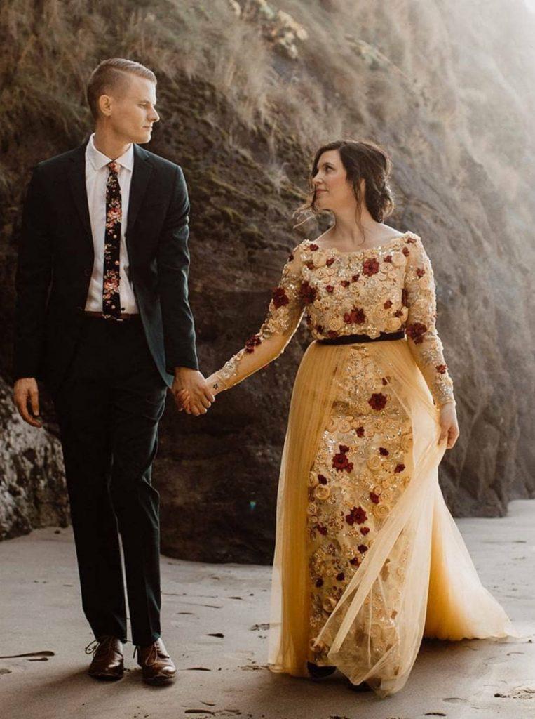 bride wearing golden wedding dress holding groom's hand