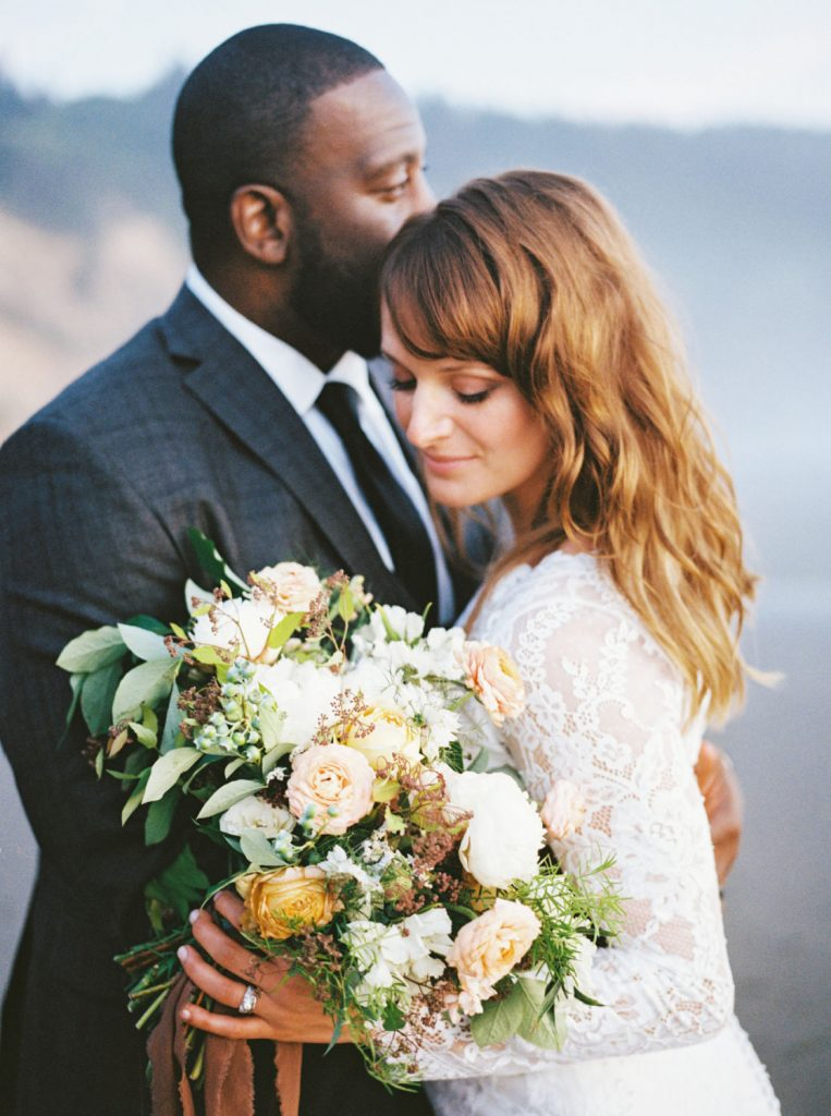 close up portrait of bride holding sea of roses bouquet with groom behind her