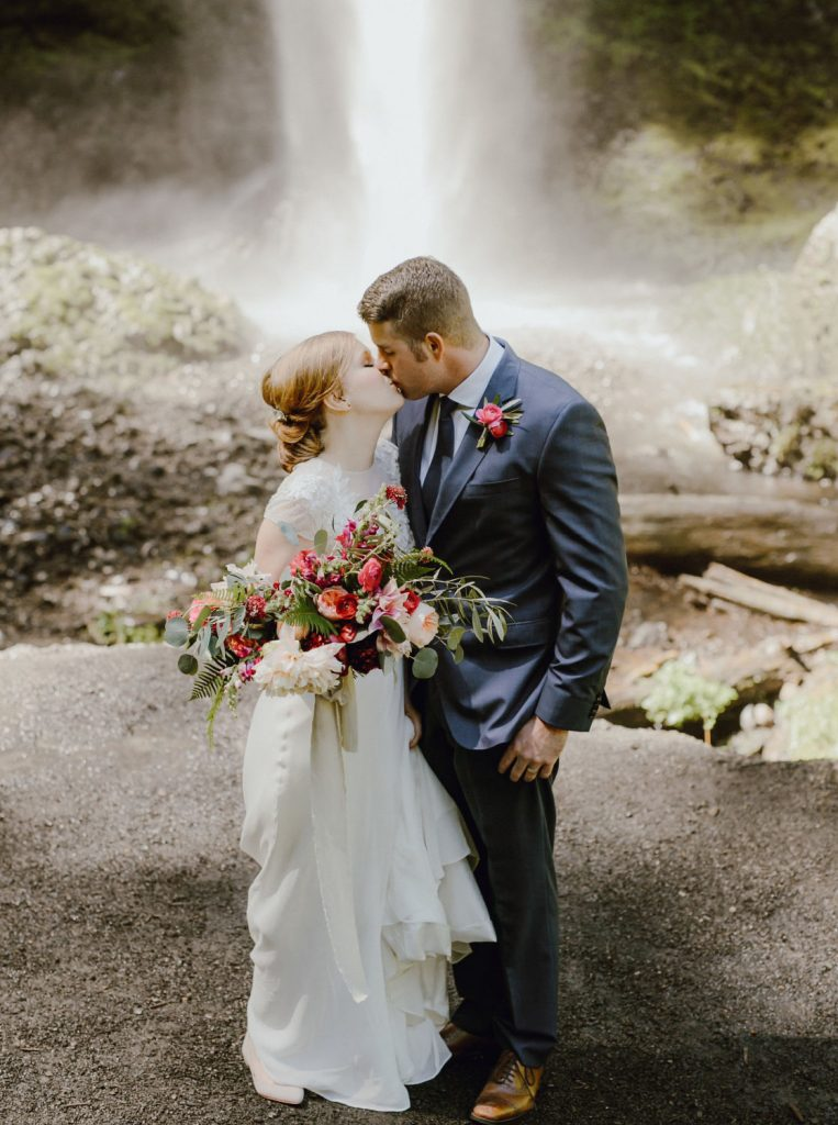 couple kissing in front of waterfall after eloping