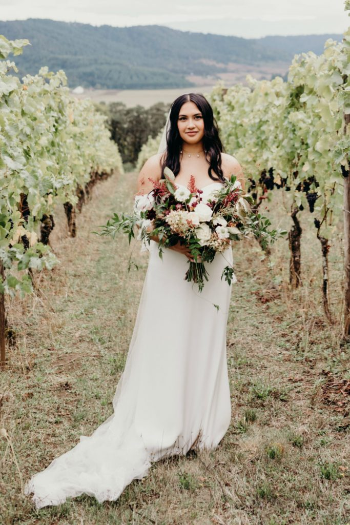 bride standing in vineyard rows holding fall bouquet