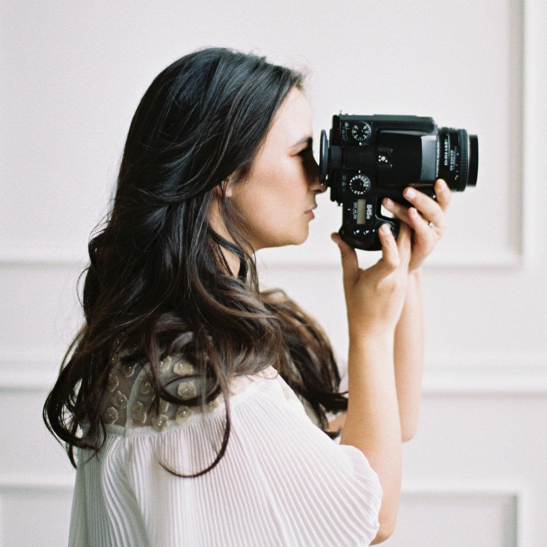 close up of photographer holding Pentax film camera