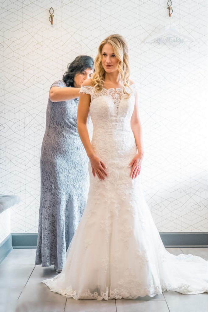 bride getting buttoned into her dress by her mother in the bridal suite of The Evergreen
