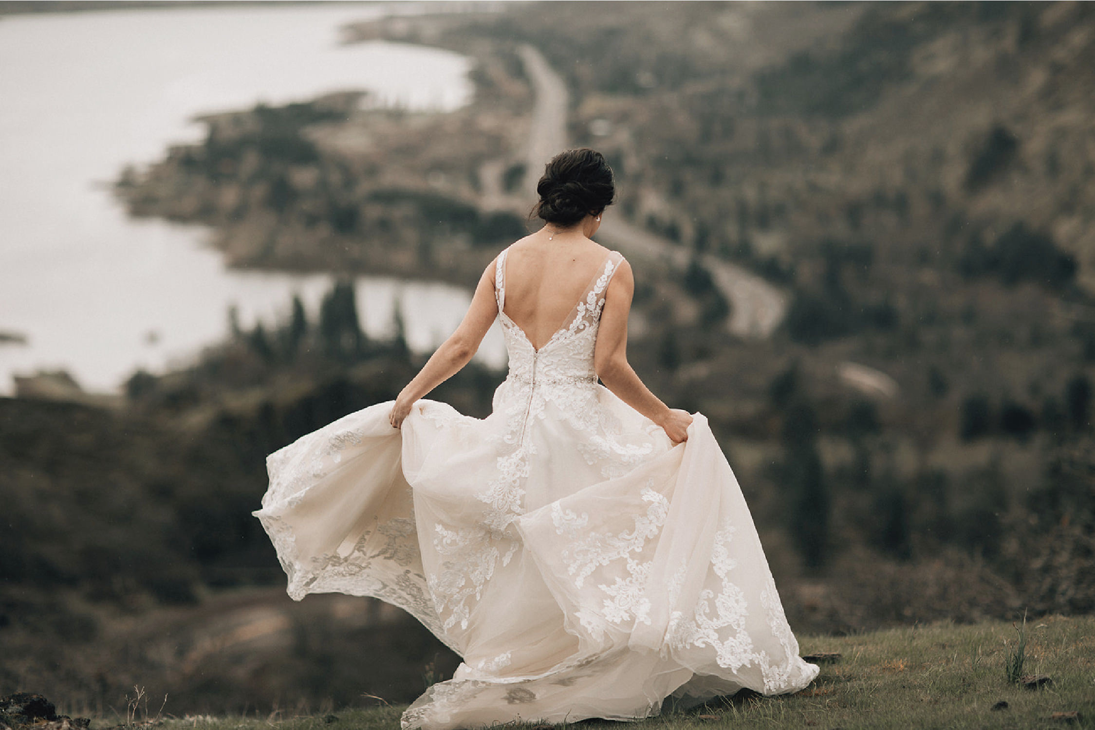 back of bride's hairstyle and dress as she walks away with mountains and river in background