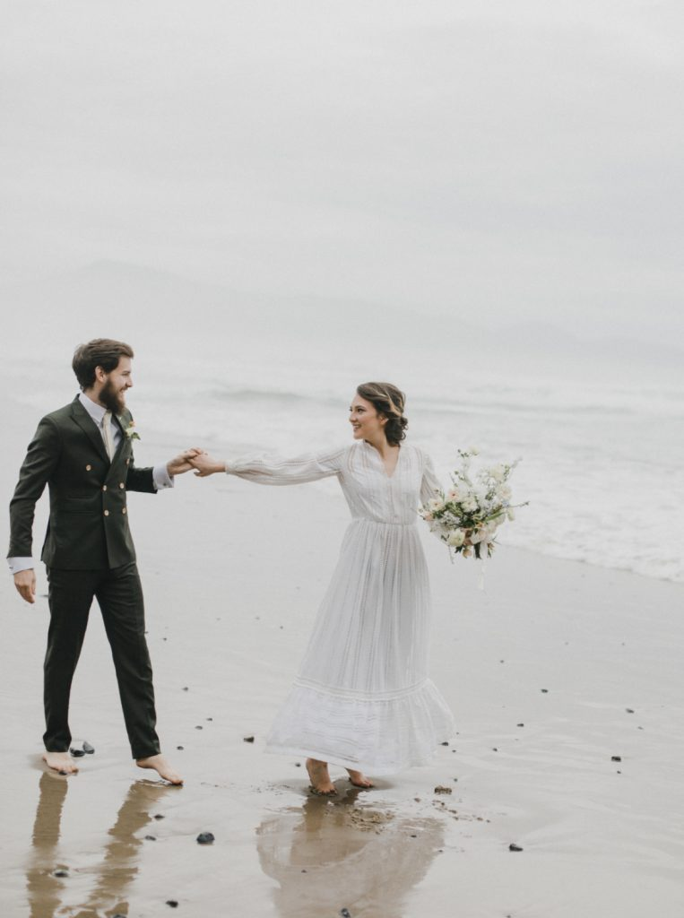 couple walking barefoot at beach after eloping