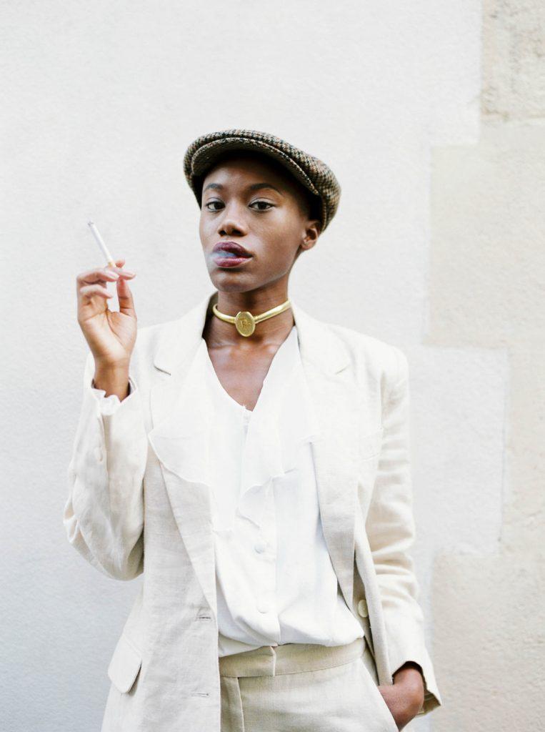 Parisian smoking wearing linen suit and tweed cap