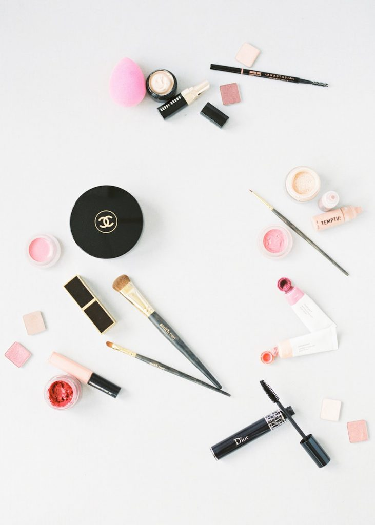 Chanel Glossier Bobbi Brown Dior Beauty Blender Tom Ford RMS Temptu and Viseart Cosmetics arranged in a flatlay