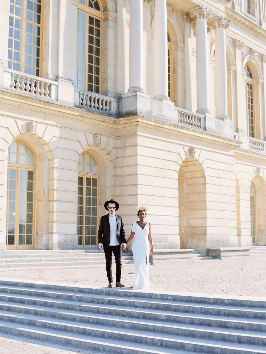 woman dressed as queen with husband in front of Chateau de Versailles