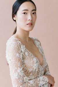 bride wearing Emily Riggs gown and natural makeup look for face