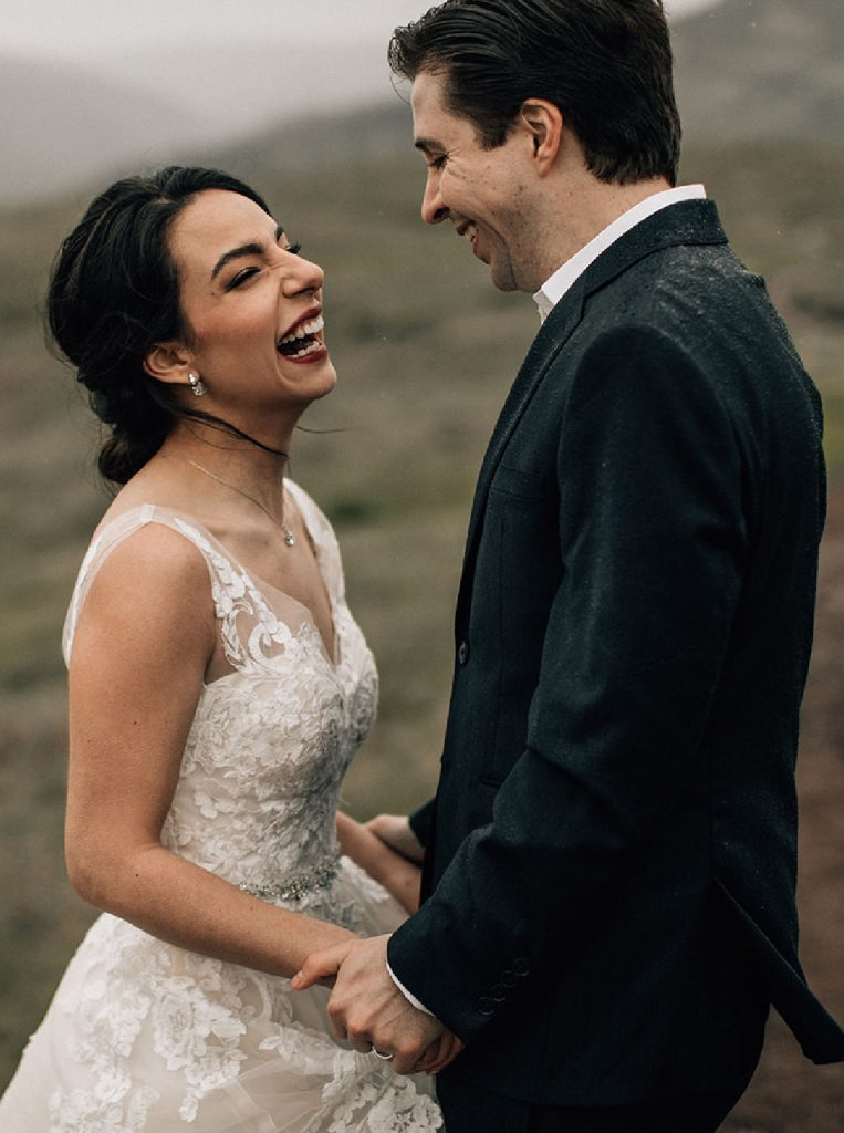 couple laughing in the rain while eloping